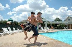 Boys Being Boys. 3 image series of two teenage boys throwing one into the pool. Boys having fun Stock Photo