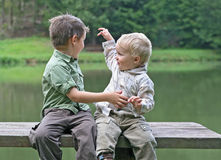 Boys on a bench at the pond Royalty Free Stock Photo