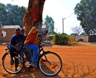 Boys on Bike - Metarica Mozambique. Three young boys playing on a bicycle in the main street of the Niassa Province village of Metarica in northern Mozambique Stock Photo