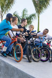 Boys on bikes at skate park event. Group of boys on bicycles chat at the skate park stock photos
