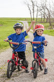 Boys on bikes. Two boys wearing helmets, and sitting beside each other with their hands in the air, on their bikes royalty free stock photography