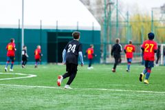 Boys at black red sportswear run, dribble, attack on football field. Young Soccer players with ball on green grass. Training. Football, active lifestyle for royalty free stock photography