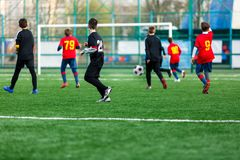 Boys at black red sportswear run, dribble, attack on football field. Young soccer players with ball on green grass. Training. Football, active lifestyle for royalty free stock image