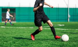 Boys at black sportswear run, dribble, attack on football field. Young soccer players with ball on green grass. Training royalty free stock image