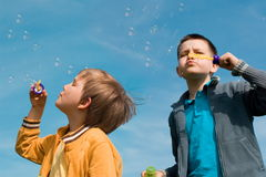Boys blowing bubbles Stock Photos