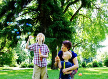 Boys blowing bubbles. In park Stock Photo