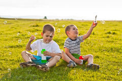 Boys blowing soap bubbles Stock Image