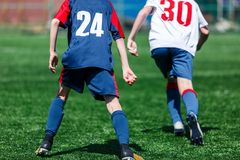 Boys at blue white sportswear run, dribble, attack on football field. Young soccer players with ball on green grass. Training royalty free stock images