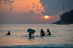 Boys on boards in sunset Royalty Free Stock Images