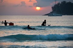Boys on boards in sunset Stock Images