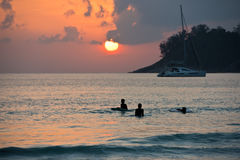 Boys on boards in sunset Royalty Free Stock Photography