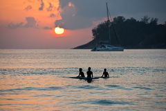 Boys on boards in sunset Stock Photography
