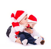 Boys brothers in santa's hats hugging Stock Photo