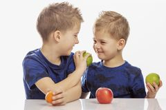 Boys brothers are sitting at the table, laughing and feeding each other fruit, close-up. Isolated on a white background stock photos