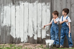Boys with brushes and paint at an old wall Stock Photos