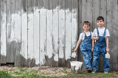 Boys with brushes and paint at an old wall Royalty Free Stock Image