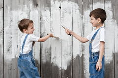 Boys with brushes and paint at an old wall Royalty Free Stock Photography