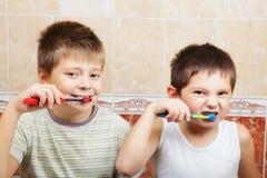 Boys brushing teeth. In bathroom closeup photo stock image