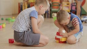 Children Kid and Baby Play With Blocks. Boys Build Toy. Children Kid and Baby Play With Blocks. Educational Toys for preschool and kindergarten child. Brothers stock footage