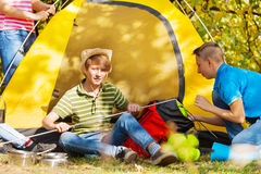 Boys build yellow tent themselves at camping site Stock Images