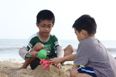 Boys Building Sand Castle. Two boys with scoops while attempting to build a sand castle at a sandy beach Stock Images