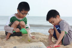 Boys Building Sand Castle. Two boys with scoops while attempting to build a sand castle at a sandy beach Stock Image