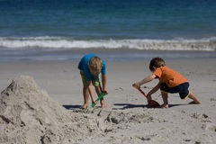 Boys building sand castles on the beach Royalty Free Stock Photo