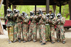 Boys in camouflage stand with paintball guns Stock Photography
