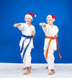The boys in caps of Santa Claus hit punch hand Royalty Free Stock Photography