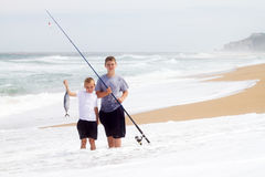 Boys catching big fish. Two boys catching a big fish on beach royalty free stock photos