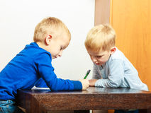 Boys children with pen writing doing homework. At home. Stock Photo