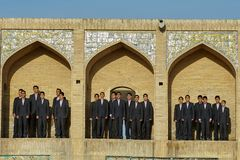 Boys` choir sings in niches of Khaju bridge, Isfahan, Iran. Isfahan, Iran - April 24, 2017: Choral singing outdoors, boys in school uniform stand in the niches stock image