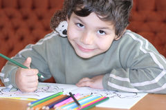 Boys with a color for drawing. Little boy line of pastel colors in coloring book Stock Image