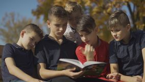 Boys company sitting on the bench and riding one book. Friends spend time riding book on a sunny day in the autumn park. stock video