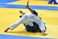 Boys compete in Judo. Two boys judoka in kimono compete on the tatami Stock Images