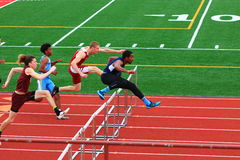 Boys competing in hurdles at a Track Competition Royalty Free Stock Photos