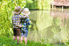 Boys in cowboy hats. Boys standing near the pond. One of them put his hand on the shoulder of another. Children dressed in the colours of the Ukrainian flag Stock Photos