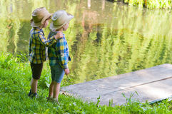 Boys in cowboy hats. Boys standing near the pond. One of them put his hand on the shoulder of another. Children dressed in the colours of the Ukrainian flag Royalty Free Stock Image