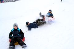 The boys crashed into each other, sledding down a snow hill. Winter fun. The action takes place on the outskirts of the city of Monino. Residents of the town royalty free stock image