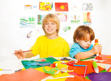 Boys cut draw and glue. Two little brother boys sketch, draw cut and glue paper together Stock Images