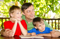Boys and dad reading Stock Photos