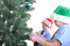 Boys decorating a Christmas tree Royalty Free Stock Images