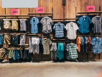 Boys department in clothing store. Shop of men`s clothing. Showcase rack with shirts. Shelves with clothes. The interior. Of the store with clothes. Clothes Royalty Free Stock Images