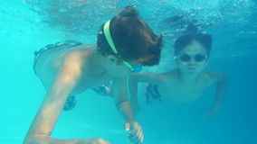 Boys dive into the pool view underwater. Two young boys dive into the pool  view underwater stock video footage