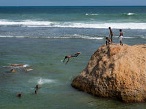 Boys dive from a rock into the sea in front of the fort of Galle Royalty Free Stock Photography
