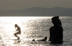 Boys Dive into the Sea of Japan off the Coast of Vladivostok, Russia. Children dive off of a wooden statue and into the sea off the coast of Vladivostok, Russia royalty free stock images