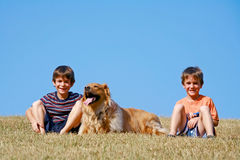 Boys and Dog. Sitting on the Side of a Hill stock photos