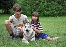 Boys with dog. Two boys with dog on the green grass Royalty Free Stock Photography