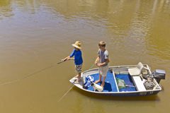 Boys and dog fishing in boat in flooded river. Royalty Free Stock Photography
