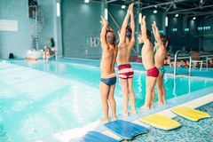 Boys doing sportive exercises with hands up. Near pool, view from back. Sporty kids preparing for swim. Kids doing exercise near sweeming pool. Healthy and Stock Photo